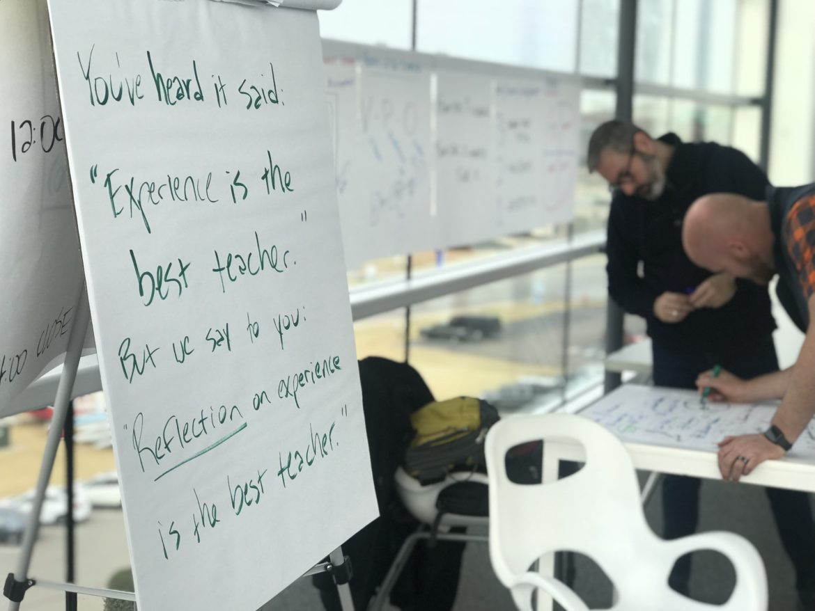 "In a classroom, a written sign reads ""You have heard it said that experience is the best teacher, but I say to you that reflection on experience is the best teacher,"" while in the background two men discuss something by a table."