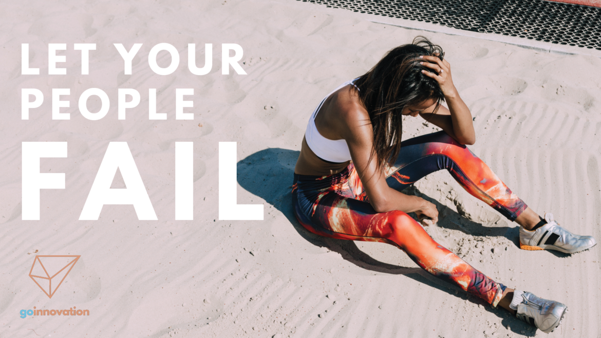 "A young African-American woman wearing track and field gear sits in the long jump sand pit with one hand on her head. She looks either exhausted or frustrated or both. The following text is overlaid on the photo: ""Let your people fail."""